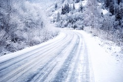 Snow-covered road in forest between mountains