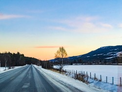 Snow-covered road through the center of Hemsedal in Viken, Norway in a winter landscape.