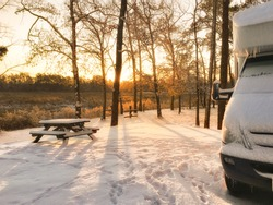 Snow covered RV camper at sunrise enjoying some winter camping at a campground with a picnic table in the background.