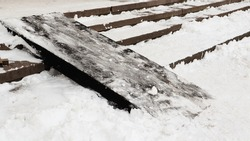 Snow covered slippery concrete stairs and wooden ramp. First snow on granite stone steps