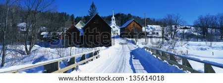 Snow covered small town in New England with white Methodist Church