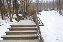 Snow covered stairs near the ice slope. Winter parkland.