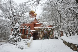 Snow-covered stone steps leading to tree-surrounded Church of the Icon of Mother of God