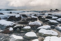 Snow covered stones at winter coast, Norway