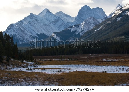 Snow covered valley with rockies on background