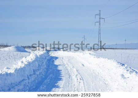 Snow-covered winter road with power line in the field, Russia