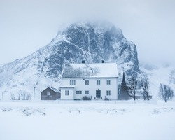 snow covered winter scene in Norway Lofoten panorama with white traditional house  build from wood