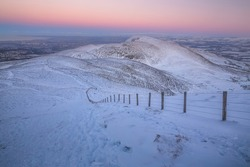 Snow covered wintery landscape view of the Pentland Hills Regional Park from atop Allermuir Hill at sunset near Edinburgh, Scotland.
