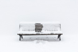 snow-covered wooden bench with an imprint of someone, who had been sitting in the middle; it seems, it was winter and she has gone