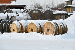 Snow-covered wooden spools with electric cable. Different size coils outdoors.  Electrical cable plant