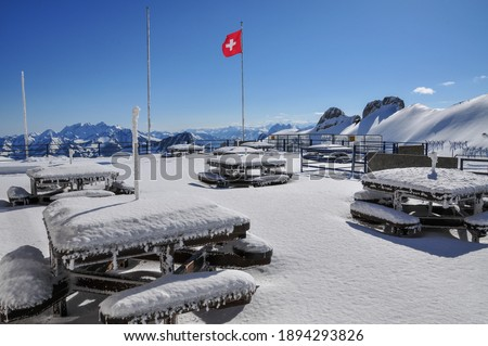Snow-covered wooden tables and benches plus a Swiss flag on the panorama terrace of viewpoint Rochers-de-Naye above Montreux, Lake Geneva, Switzerland. This was shot in late April. Photo stock ©