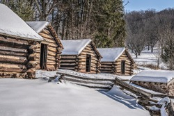 Snow coveres log cabins at Valley Forge National Park in Pennsylvania