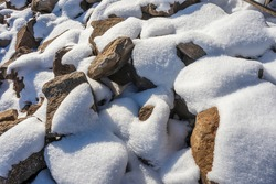 Snow covers large rough stones on a rocky shoreline on a frozen lake.