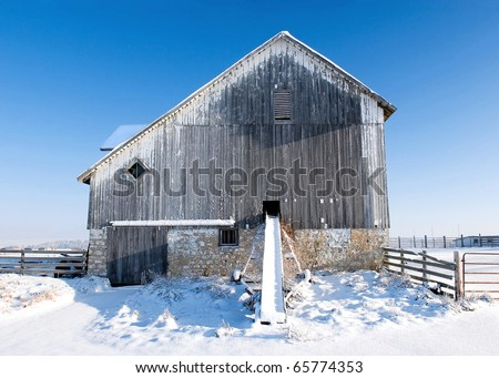 Snow drapes an old barn and farm equipment against a cold blue sky.