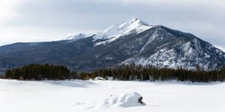Snow drifting on boulders during winter in Colorado.  Trees in the foreground of the Tenmile Mountains of Colorado.  Drifted snow on Dillon Reservoir.