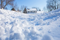 Snow drifts and chunks of snow piling up in winter with a house