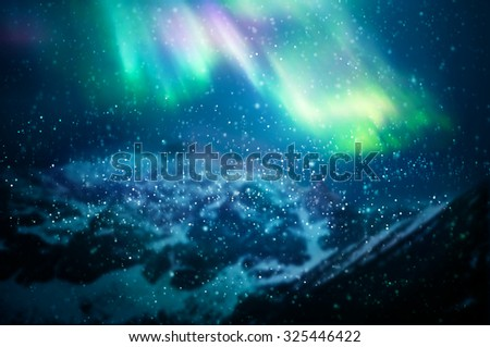 Snow falling against aurora borealis - focus on snowflakes, northern lights and mountains in the background