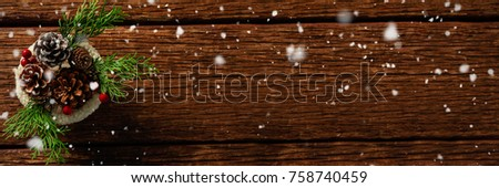 Snow falling against pine cones and twigs with cherry in bowl #758740459