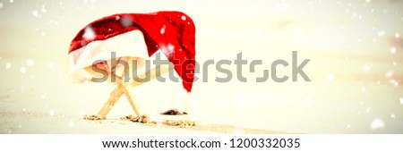 Snow falling against starfish covered with santa hat kept on sand #1200332035