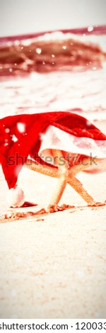 Snow falling against starfish covered with santa hat kept on sand #1200332104