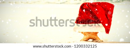 Snow falling against starfish covered with santa hat kept on sand #1200332125