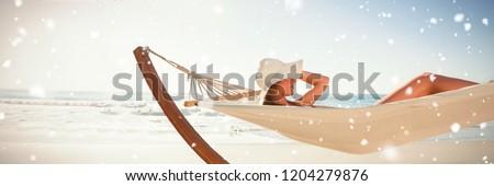 Snow falling against woman wearing sunhat and bikini relaxing on hammock