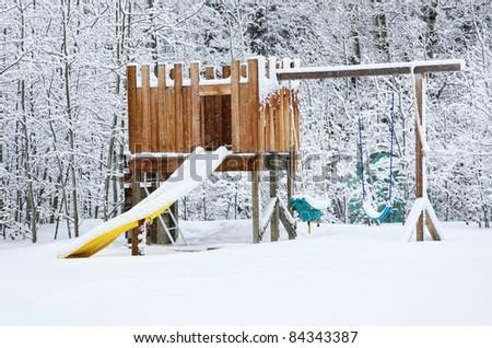 Snow falling on a backyard playset.