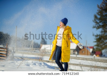 Stock Photo Snow falls on a woman in a bright yellow down-padded coat. She stands with an enthusiastic smile on her face. Fine winter day. Ground is covered by snow. Cute rustic winter landscape.