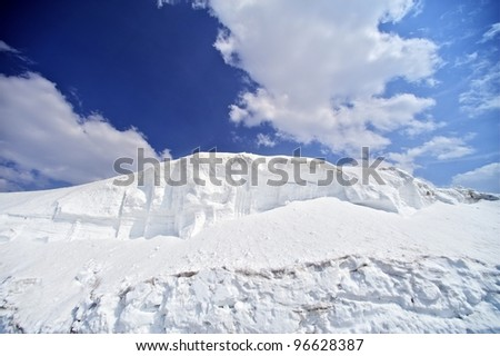 Snow Fields - Winter Background with Large Snowfields and Blue Cloudy Sky. Perfect Ski Conditions.