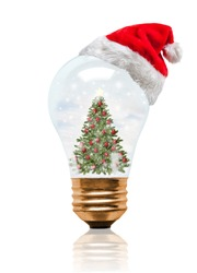 Snow globe light bulb wearing Santa hat with decorated Christmas tree and copy space. Glowing Xmas season and bright New Year.