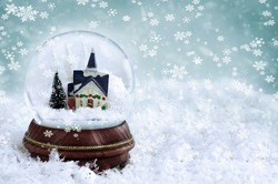Snow globe with church and Christmas trees inside. Copy space available. Shallow depth of field with selective focus on snowglobe.