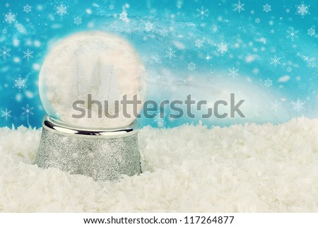 Snow globe with snow covered pine trees inside. Copy space available.