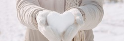 Snow heart in hands. Human hands in warm beige gloves with snowy heart. I love winter or St.Valentine's Day romantic creative concept.