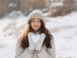 Snow heart in woman's hands outdoors. Girl on stylish winter clothes hat, warm beige gloves holding snowy heart with closed eyes against a nature winter background. I love winter or St.Valentine's Day