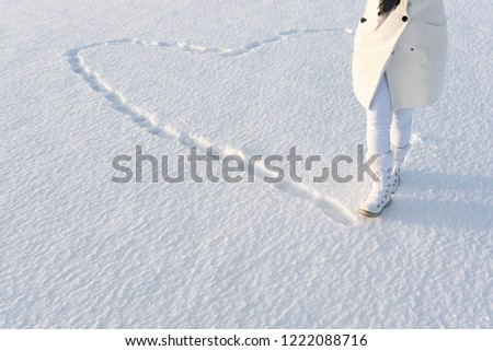 Snow heart made by feet traces. Anonymous woman dressed in white winter coat, walks on snow cover in snow boots. #1222088716
