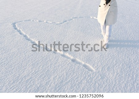 Snow heart made by footsteps. Anonymous woman dressed in white winter coat, walks on deep snow in snow boots. #1235752096