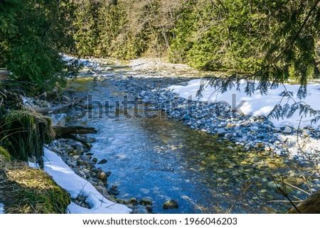 Snow lines the shore of Denny Creek in Washington State. Zdjęcia stock ©