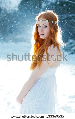 Snow Maiden. Fantasy image of beautiful red head woman standing in snow, looking at camera