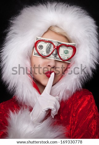 Snow maiden in glasses with dollars, covering the eye shows a sign of silence on a black background