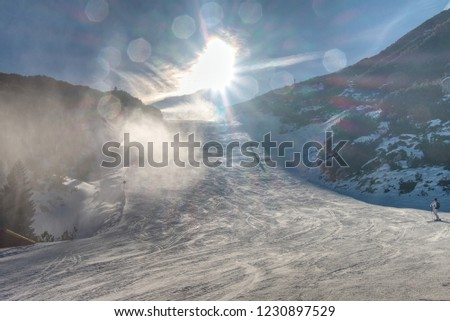 Snow maker machine works (snow gun or snow cannon) at ski slopes resort - standard equipment device for making snow to create better skiing conditions  #1230897529