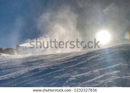Snow maker machine works (snow gun or snow cannon) at ski slopes resort - standard equipment device for making snow to create better skiing conditions  #1232327836