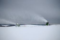 Snow making machine on the ski slope in winter. Spraying snow powder. White stream of snow on the background of the cloudy sky.