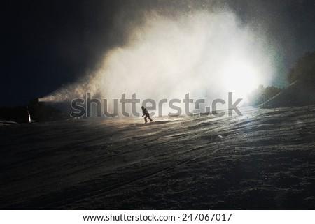 Snow making on slope. Skier near a snow cannon making fresh powder snow. Mountain ski resort and winter calm mountain landscape.