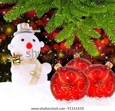 Snow man with red glass Christmas balls and by the branches of pine