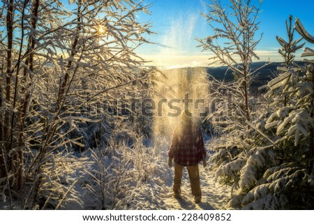 snow mountain landscape with a person with snow above him and sun beams