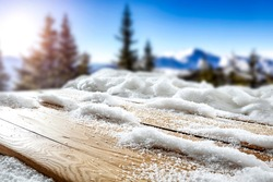 Snow on a wooden table in alpine mountain surroundings on a beautiful winter day