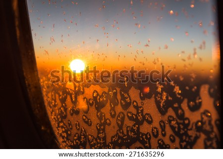 snow on plane window with sun rise background