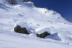 snow on stones, Arabba; bright snow forms smooth waves on stones in slope in Dolomites, shot under deep blue sky