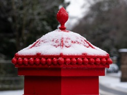 snow on the top of a Victorian postbox