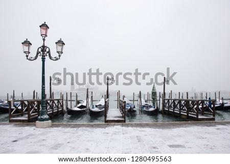 Snow on Venetian Gondolas, Grand Channel Italy - snowing in Venice with gondolas on Grand Channel, St. Mark square, Italy, march 2018 #1280495563